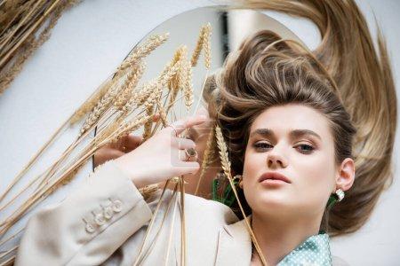 Draufsicht auf junge Frau, die in der Nähe von Weizenstacheln und Spiegel auf Weiß liegt