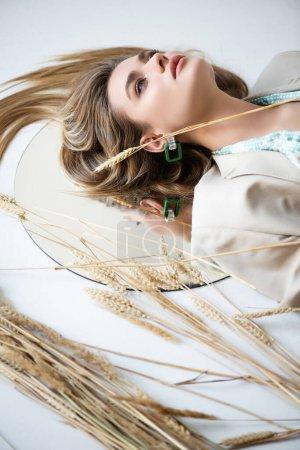 junge Frau liegt in der Nähe von Weizen und Spiegel, während sie auf weiß schaut