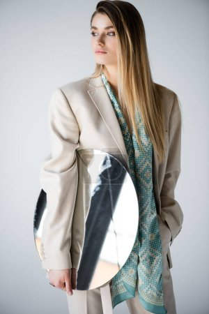 stylish woman in suit holding round mirror while looking away on grey