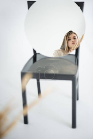 reflection of young woman looking at camera near wheat with blurred chair on white background