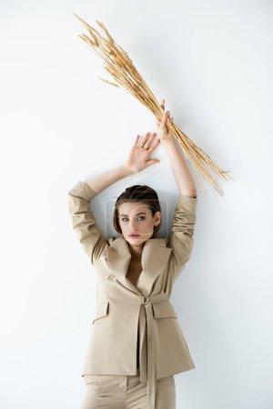 mujer joven en ropa formal beige sosteniendo el trigo por encima de la cabeza en blanco
