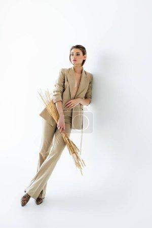 longueur totale de la jeune femme en tenue de cérémonie beige posant tout en tenant du blé sur blanc