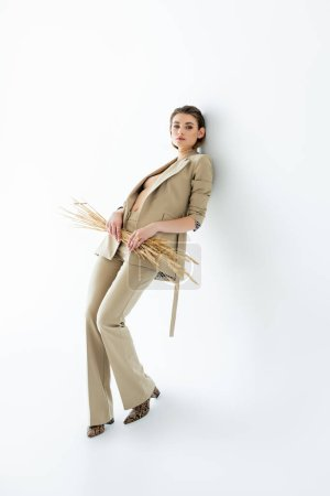 full length of young model in beige suit posing while holding wheat on white