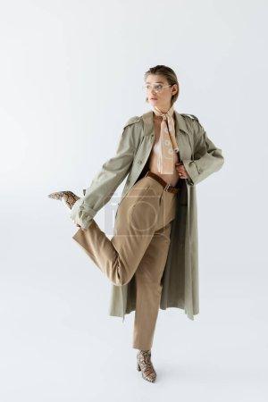 Photo pour Pleine longueur de femme à la mode dans des lunettes, trench coat et écharpe posant sur blanc - image libre de droit