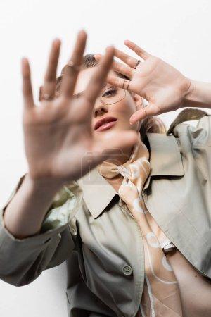 Photo pour Vue de dessus de la jeune femme en lunettes, trench coat et écharpe couché tout en faisant un geste sur blanc - image libre de droit