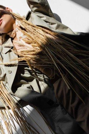 vista recortada de mujer joven en gabardina y bufanda tendida cerca de trigo sobre blanco