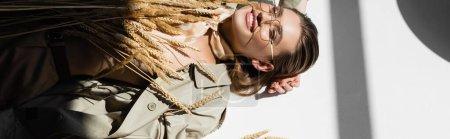 Hochwinkelaufnahme einer fröhlichen Frau mit Brille, Trenchcoat und Schal, die neben Weizen auf Weiß liegt, Banner