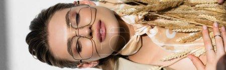 vue du dessus de la femme heureuse dans les lunettes et l'écharpe couché près du blé sur blanc, bannière