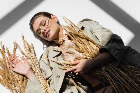vue du dessus de la femme heureuse dans des lunettes, trench coat et écharpe couché près du blé sur blanc