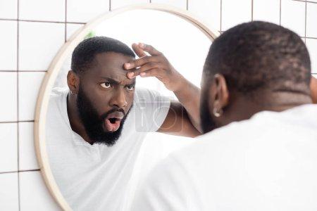 Photo pour Choqué afro-américain homme regardant les rides dans le miroir - image libre de droit