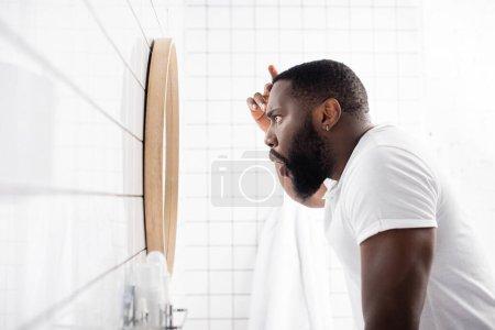 Photo pour Vue latérale de l'homme afro-américain regardant les rides dans le miroir - image libre de droit