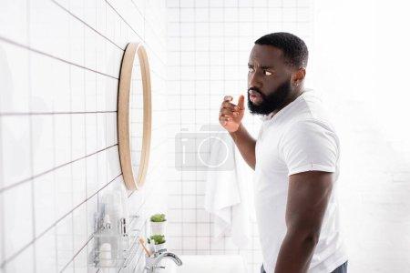 Photo pour Afro-américain homme regarder visage dans miroir - image libre de droit