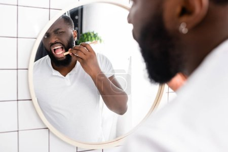 afro-american man checking gum with bamboo toothbrush
