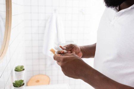 Photo pour Vue recadrée de l'homme afro-américain serrant le dentifrice hors du tube - image libre de droit