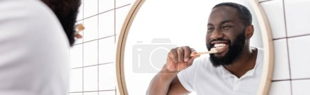 Photo pour Plan panoramique d'un homme afro-américain brossant des dents avec une brosse à dents en bambou - image libre de droit
