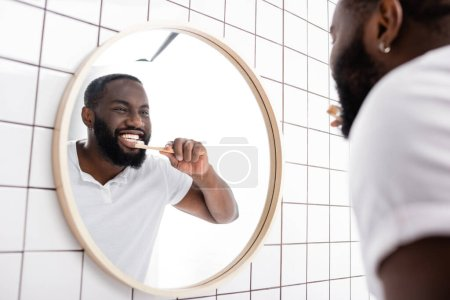 Photo pour Miroir reflet de l'homme afro-américain brossant les dents dans la salle de bain - image libre de droit