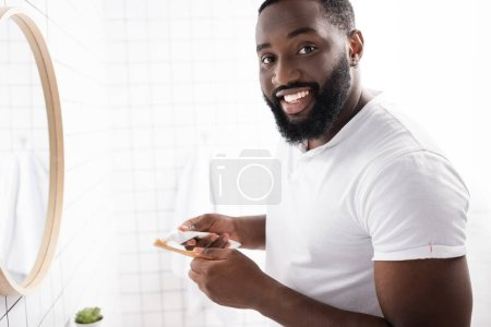 Photo pour Souriant afro-américain homme pressant le dentifrice et regardant la caméra - image libre de droit