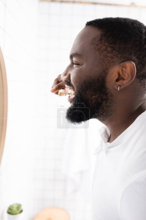 Photo for Side view of afro-american man brushing teeth with bamboo toothbrush - Royalty Free Image