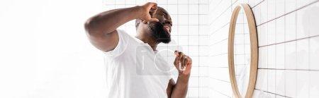 Panoramablick auf Afroamerikaner mit Zahnseide und Blick in den Spiegel