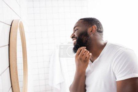 Photo pour Vue latérale de l'homme afro-américain heureux regardant dans le miroir et touchant barbe - image libre de droit
