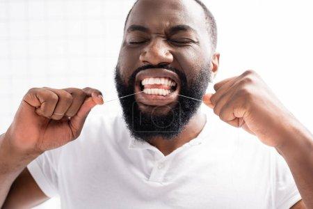 Photo pour Portrait d'un homme afro-américain les yeux fermés avec de la soie dentaire - image libre de droit