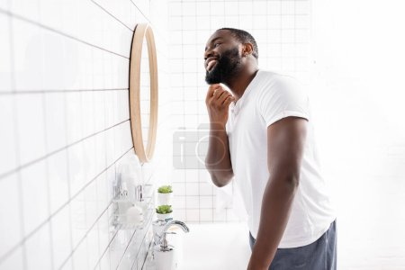happy afro-american man looking in mirror and touching beard in bathroom