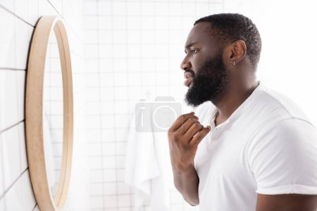 Photo for Side view of unhappy afro-american man looking at beard in mirror - Royalty Free Image