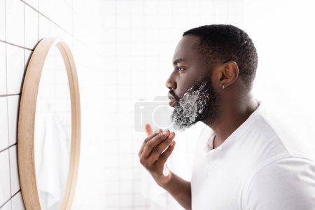 Photo pour Vue latérale de l'homme afro-américain appliquant de la mousse à raser et regardant dans le miroir - image libre de droit