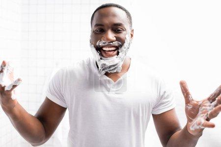 hombre afroamericano riendo con espuma de afeitar en la cara mirando a la cámara