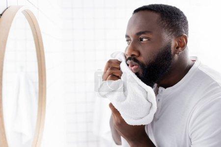 Photo pour Afro-américain homme séchage barbe avec serviette - image libre de droit