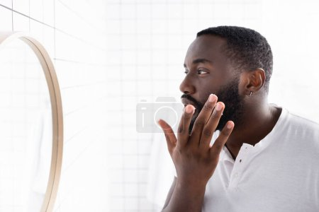 Photo for Afro-american man applying cure for strengthening beard growth - Royalty Free Image