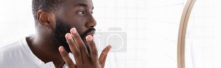 panoramic shot of afro-american man applying cure for strengthening beard growth