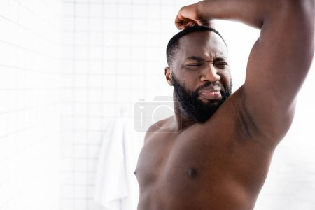Photo for Afro-american man putting hand up and grimacing from bad smell - Royalty Free Image