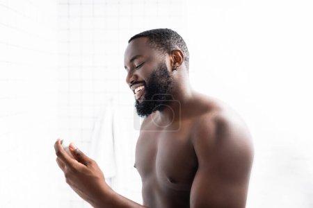 Photo pour Souriant afro-américain homme tenant déodorant dans la main - image libre de droit