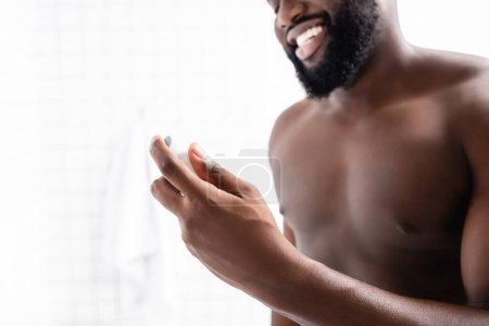 Photo for Cropped view of smiling afro-american man holding deodorant in hand - Royalty Free Image