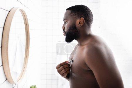 Photo pour Vue latérale de l'homme afro-américain rasage poitrine avec rasoir - image libre de droit