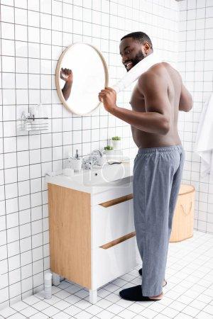 Photo pour Homme afro-américain souriant debout dans la salle de bain avec serviette derrière le cou - image libre de droit