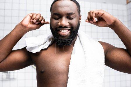 Photo pour Portrait d'un homme afro-américain nettoyant les oreilles avec plaisir - image libre de droit