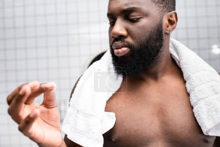 afro-american man using cure for strengthening beard growth