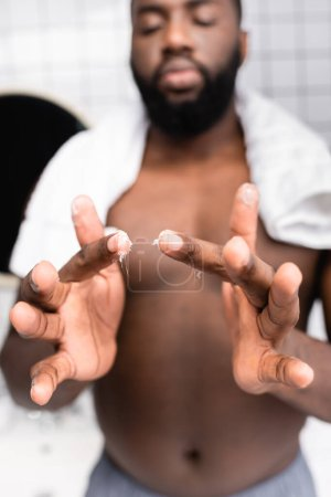 selective focus of afro-american man using cure for strengthening beard growth
