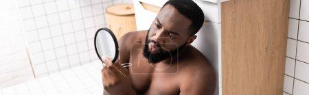 Photo pour Plan panoramique de l'homme afro-américain assis sur le sol de la salle de bain et regardant le visage dans un petit miroir - image libre de droit