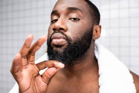 Photo pour Portrait de l'homme afro-américain utilisant un remède pour renforcer la croissance de la barbe - image libre de droit