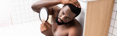 Photo pour Plan panoramique de l'homme afro-américain assis sur le sol de la salle de bain et la fixation des cheveux dans un petit miroir - image libre de droit