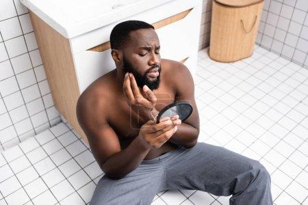 Photo pour Afro-américain assis sur le sol de la salle de bain et fixant les cheveux sur la barbe - image libre de droit