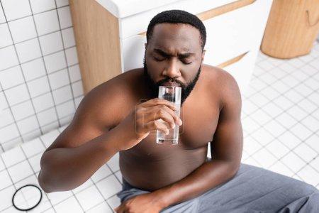 hombre afroamericano que sufre de resaca y agua potable