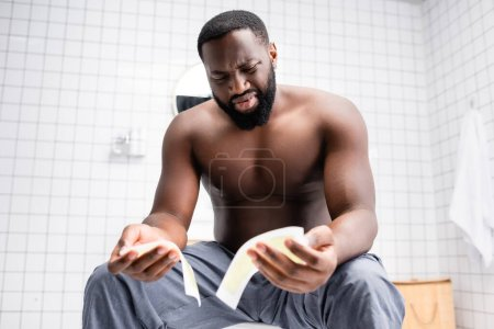 Photo pour Confus afro-américain homme essayer bandes de cire - image libre de droit