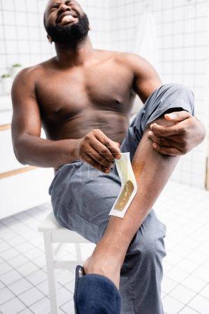 Photo pour Homme afro-américain arrachant des bandes de cire et souffrant de douleur - image libre de droit