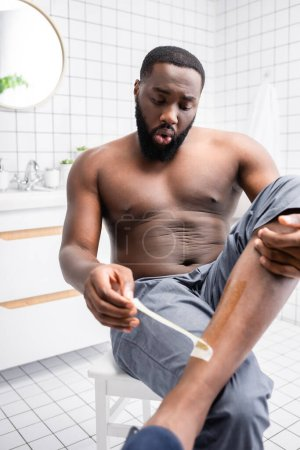 Photo for Afro-american man tearing off wax strips from leg - Royalty Free Image