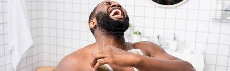 Photo pour Plan panoramique d'un homme afro-américain arrachant des bandes de cire et criant de douleur - image libre de droit