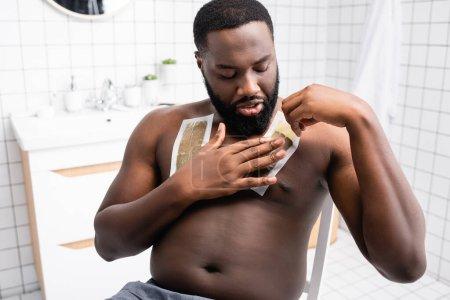 Photo pour Homme afro-américain appliquant des bandes de cire sur la poitrine - image libre de droit